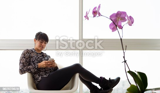29 year old woman sitting at the huge window of her living room home, working on her cell phone.