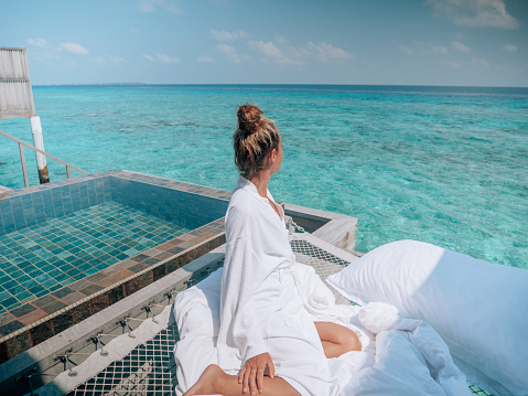 30's woman relaxing on hammock over sea in luxury private villa in the Maldives Islands