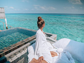 istock Woman relaxing in luxury hotel in the Maldives 1298305536