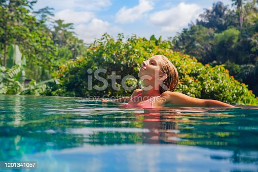 929671306 istock photo Woman relaxing in luxury spa hotel in infinity swimming pool 1201341057