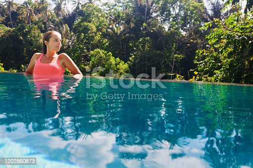929671306 istock photo Woman relaxing in luxury spa hotel in infinity swimming pool 1202860873