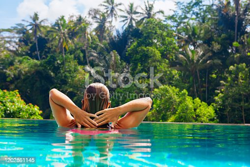 929671306 istock photo Woman relaxing in luxury spa hotel in infinity swimming pool 1202861145
