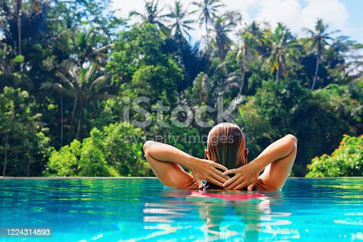 883117662 istock photo Woman relaxing in luxury spa hotel in infinity swimming pool 1224314893