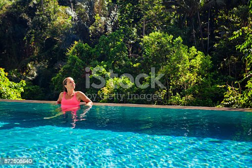 883117662 istock photo Woman relaxing in luxury spa hotel in infinity swimming pool 872508640