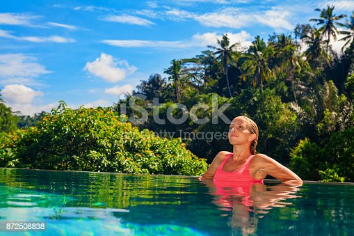 883117662 istock photo Woman relaxing in luxury spa hotel in infinity swimming pool 872508838