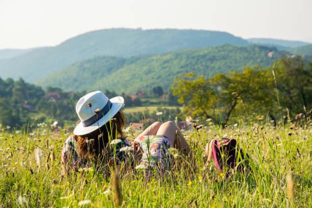 Woman relaxing in meadow stock photo