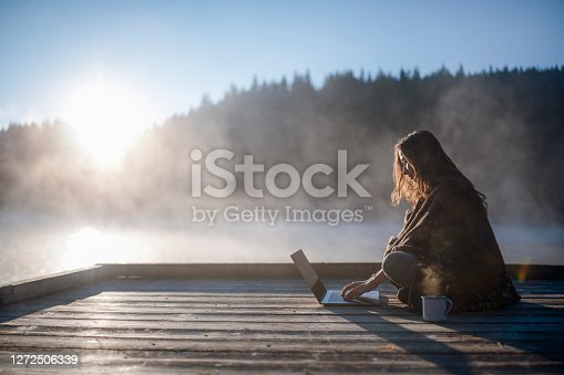 Side view of beautiful woman relaxing at sunrise with coffee and using laptop.