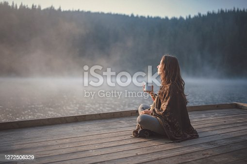 Side view of woman sitting on wooden pier in nature, she looking the sunrise and drinking coffee.