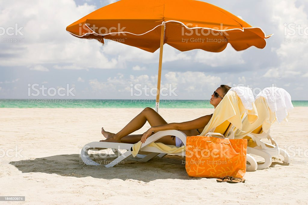 woman relaxing in recliner under the umbrella at a beach stock photo