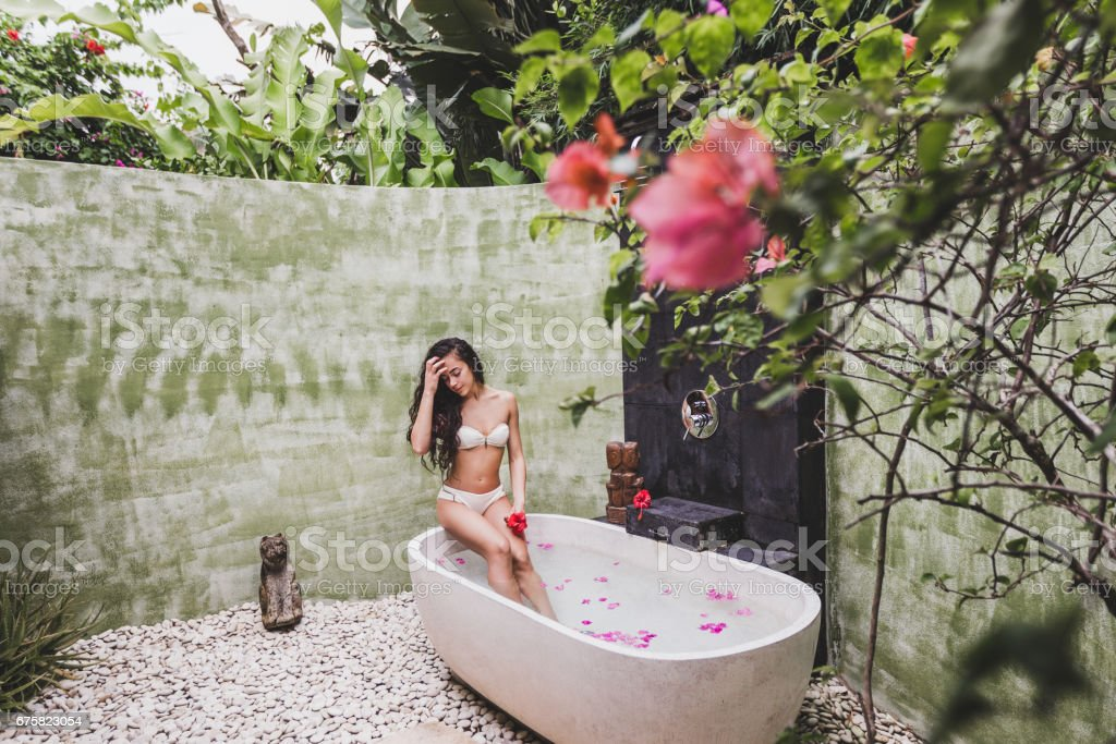 Woman Relaxing In Round Outdoor Bath With Tropical Flowers Organic