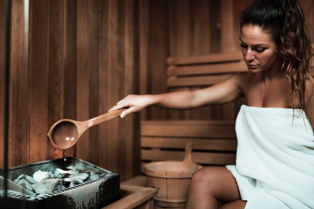 woman relaxing in sauna. - sauna foto e immagini stock