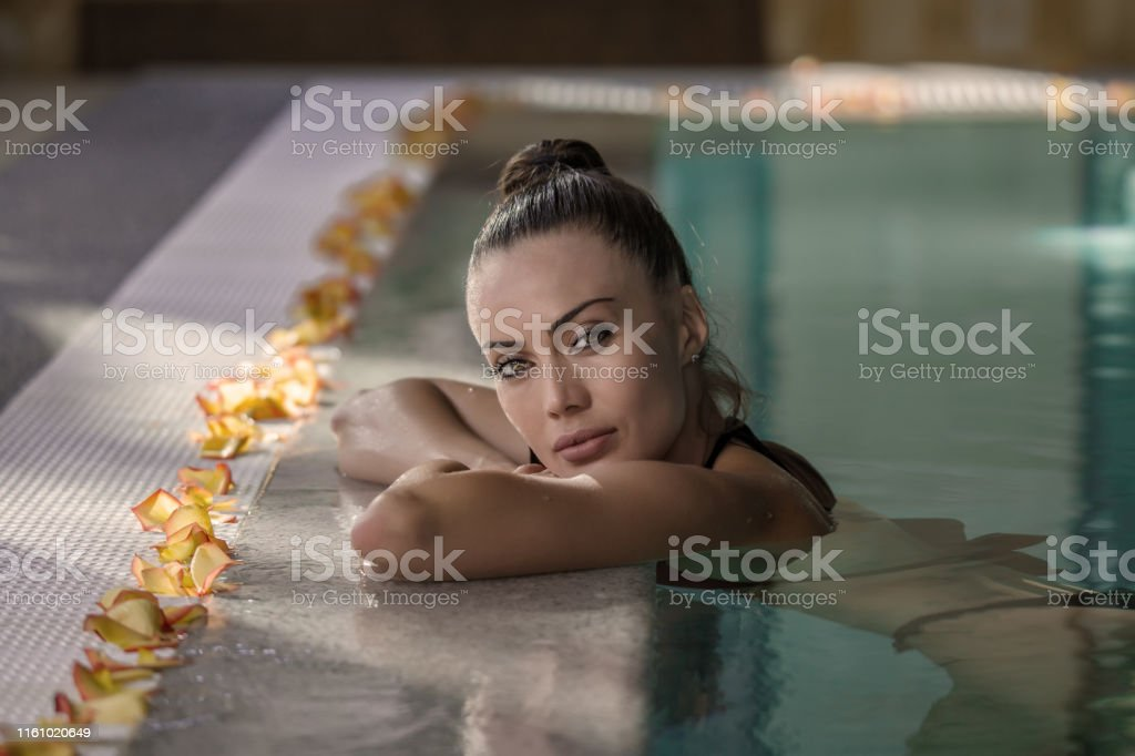 Side view of attractive female leaning on poolside and looking at...