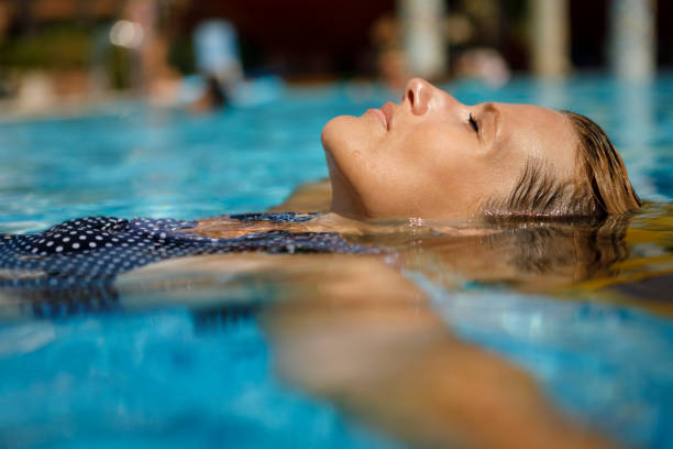 Woman relaxing in swimming pool Woman relaxing in swimming pool middle aged women in bikinis stock pictures, royalty-free photos & images
