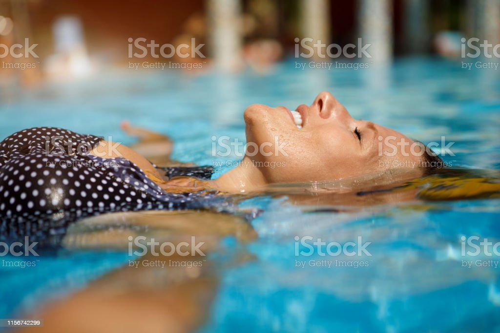 Woman relaxing in swimming pool Woman relaxing in swimming pool Adult Stock Photo