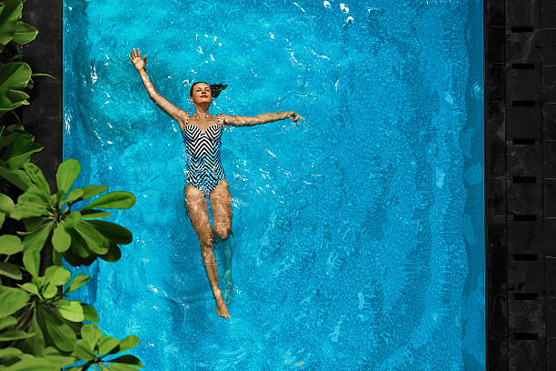Woman Relaxing In Swimming Pool Water. Summer Holidays Vacation. stock photo