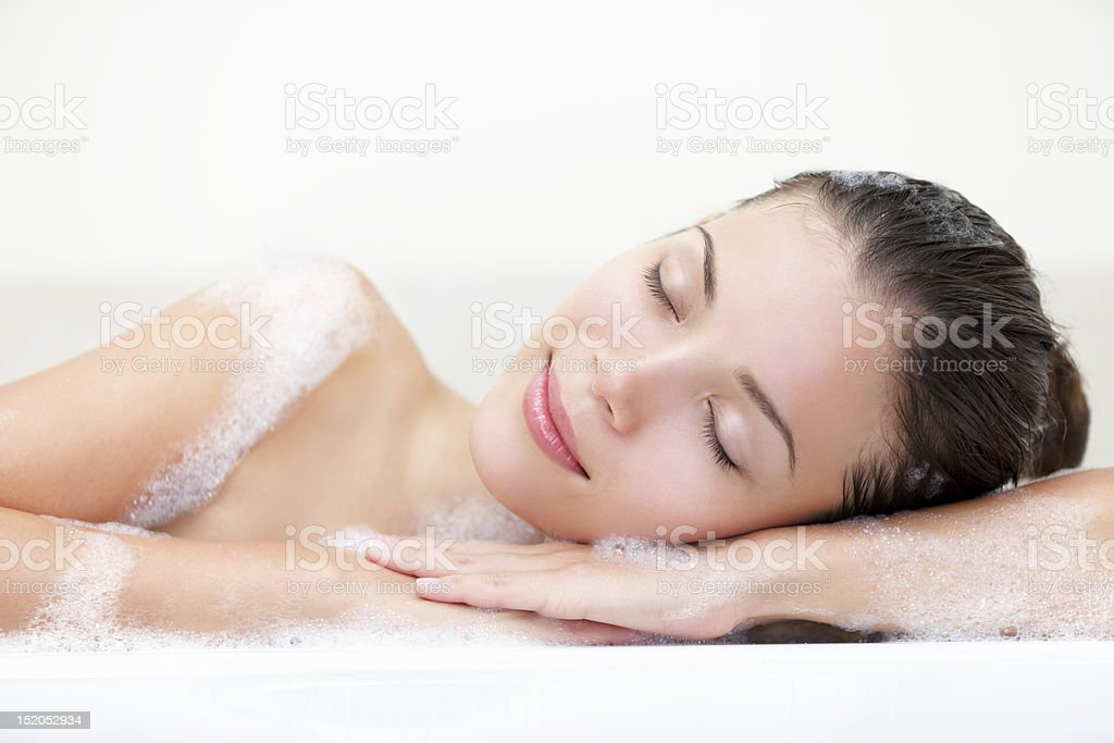 A woman relaxing in the bathtub stock photo