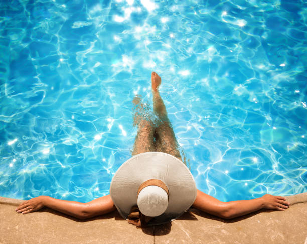 woman relaxing in the pool - taking a break stock photos and pictures