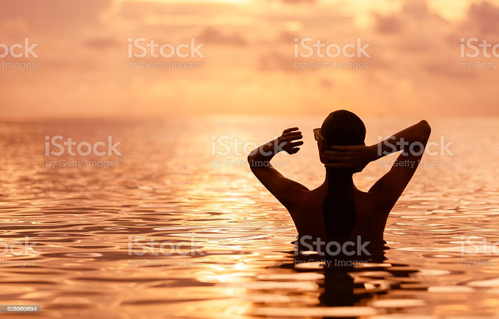 Woman relaxing in the water at sunset stock photo