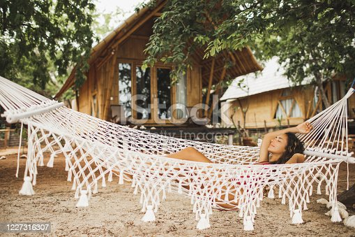817409212 istock photo Woman relaxing in the white handmade macrame hammock on tropical beach. Travel, leisure and vacations concept. 1227316307