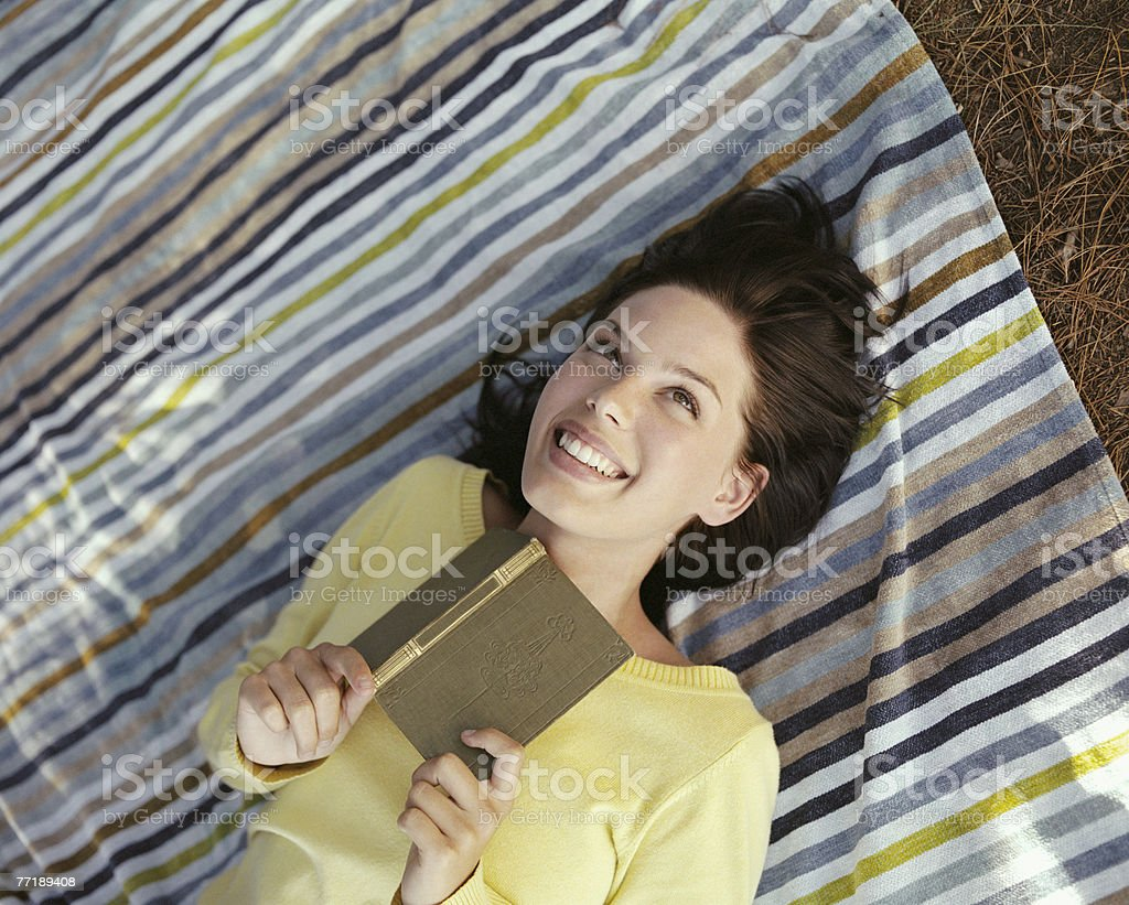 A woman relaxing in the woods reading royalty-free stock photo