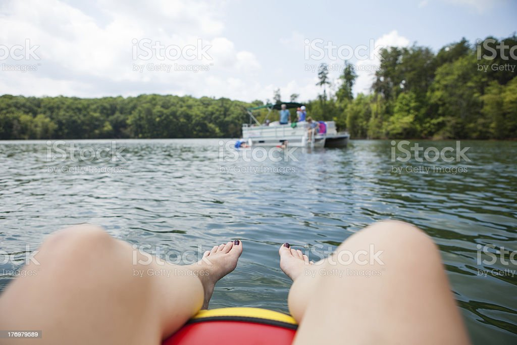 Woman relaxing in tube on lake while looking at pontoon stock photo