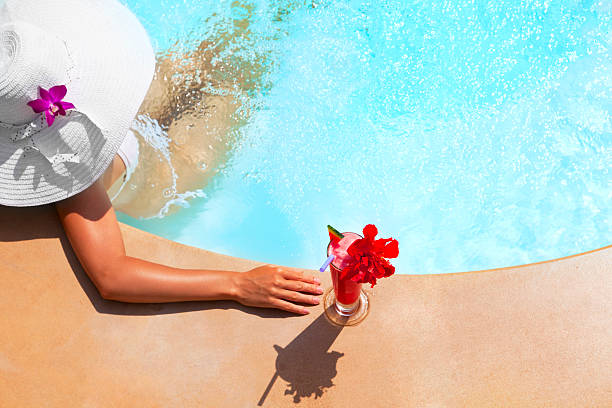 woman relaxing in waterpool woman relaxing in an outdoor waterpool sailor hat stock pictures, royalty-free photos & images