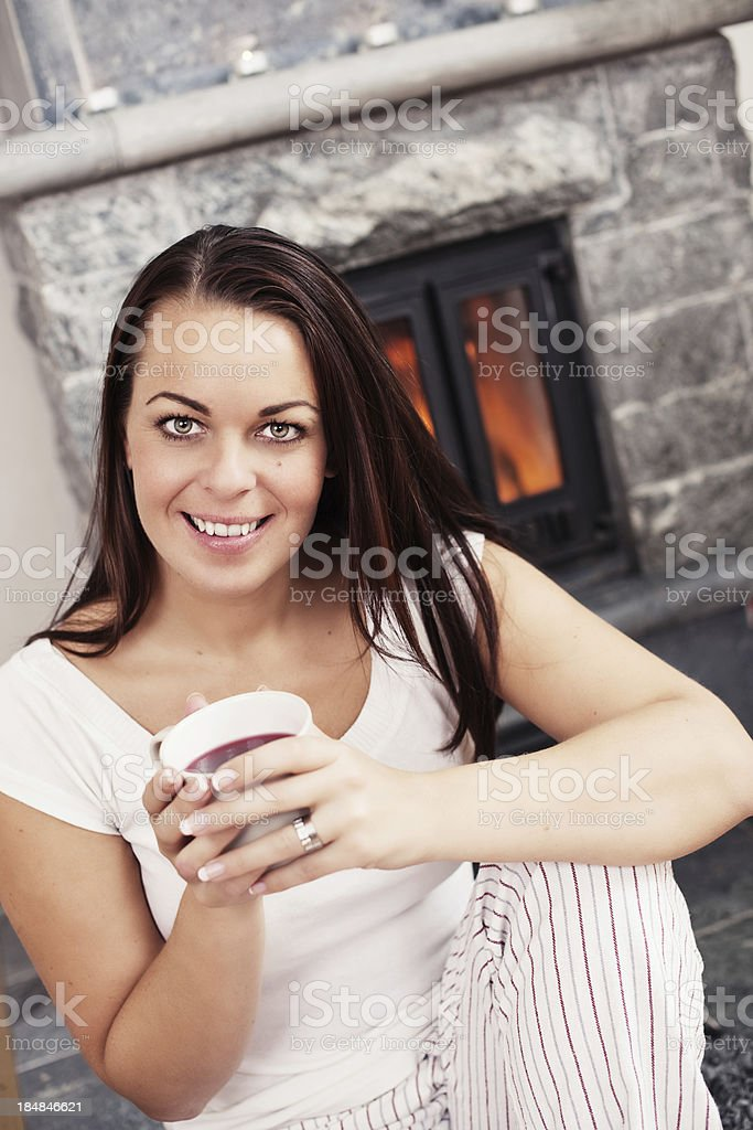 Woman relaxing infront of fireplace royalty-free stock photo