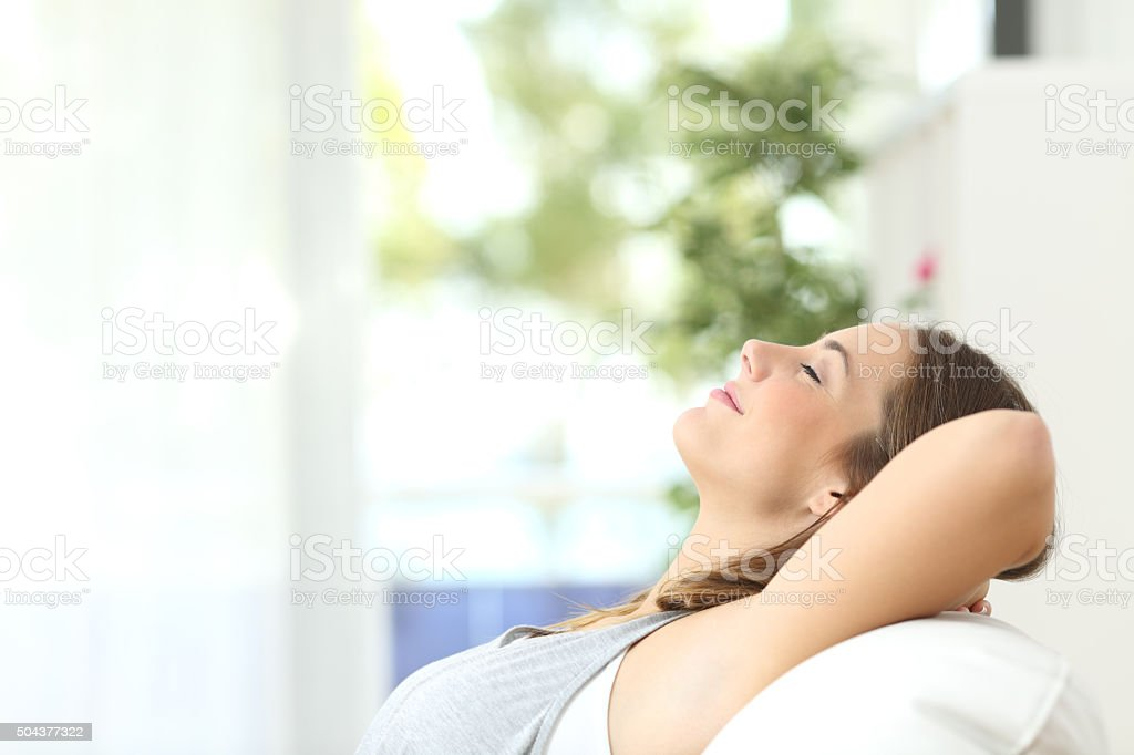 Woman relaxing lying on a couch at home stock photo