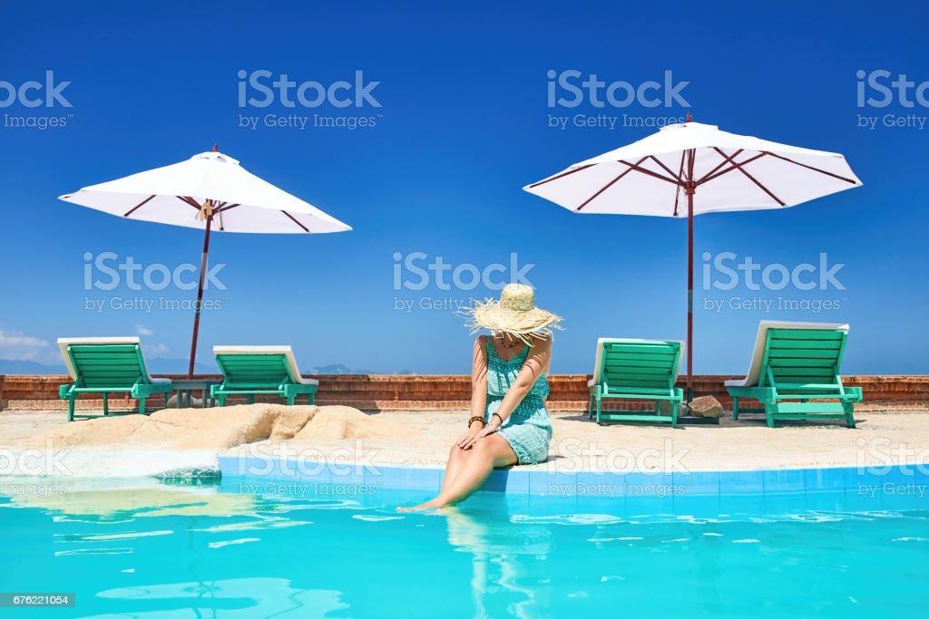 Woman relaxing near poolside on resort stock photo