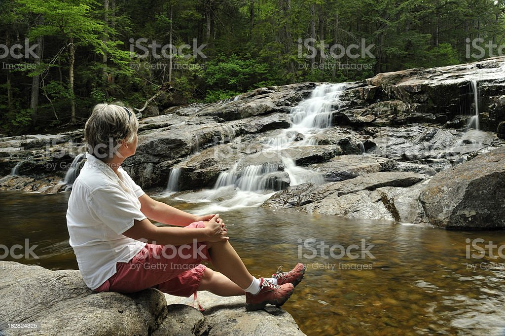 Woman relaxing near waterfall, Franconia Notch State Park, New Hampshire royalty-free stock photo