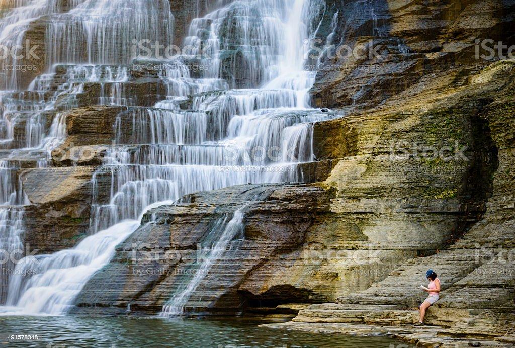 XXXL: Woman relaxing next to a waterfall stock photo
