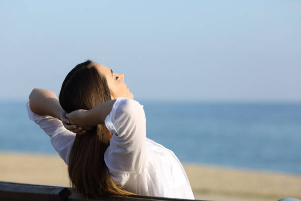 Woman relaxing on a bench on the beach stock photo