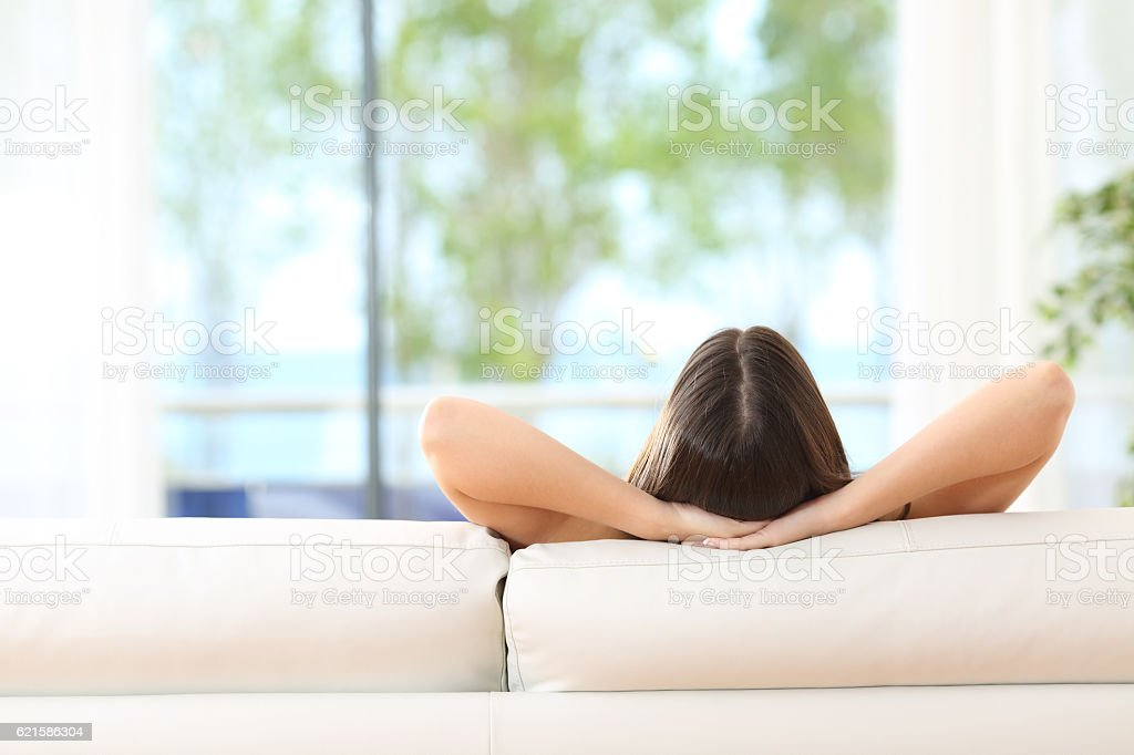 Woman relaxing on a couch at home stock photo