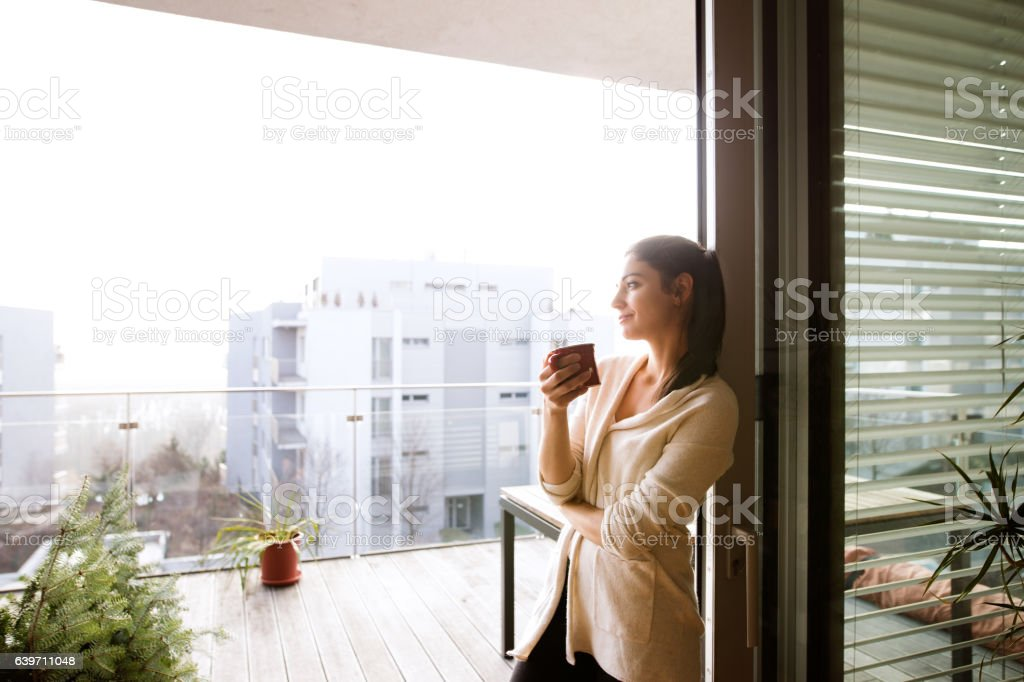 Woman relaxing on balcony holding cup of coffee or tea - foto de acervo