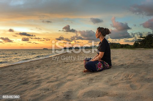 istock Woman relaxing on beach at sunset 653482360