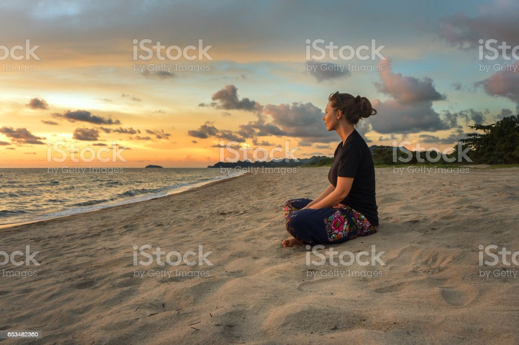 Woman relaxing on beach at sunset stock photo
