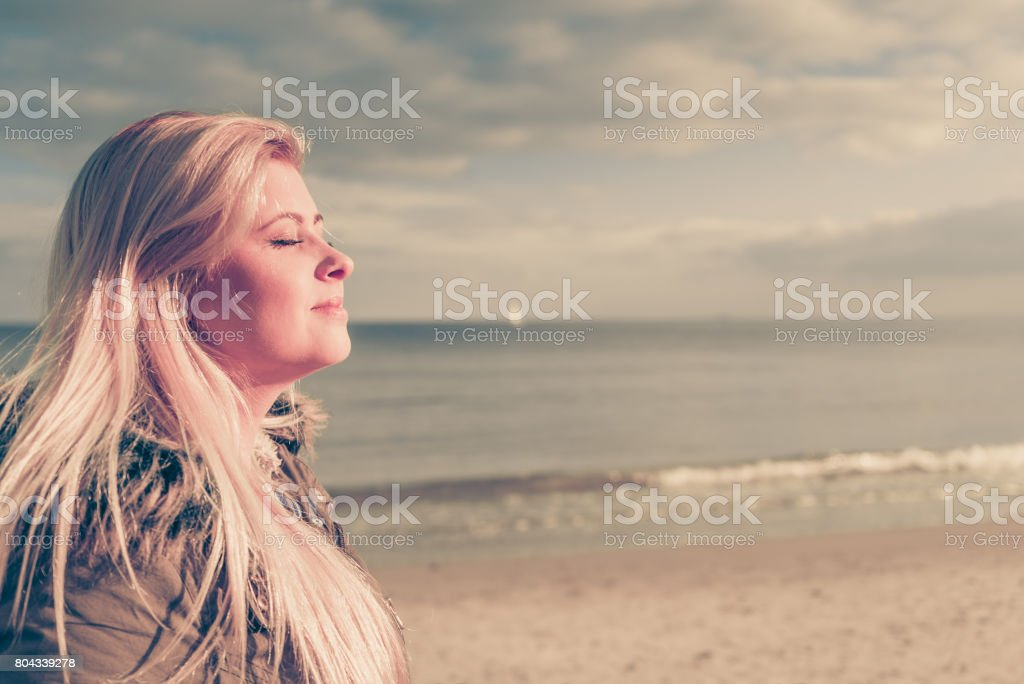 Woman relaxing on beach, cold day stock photo