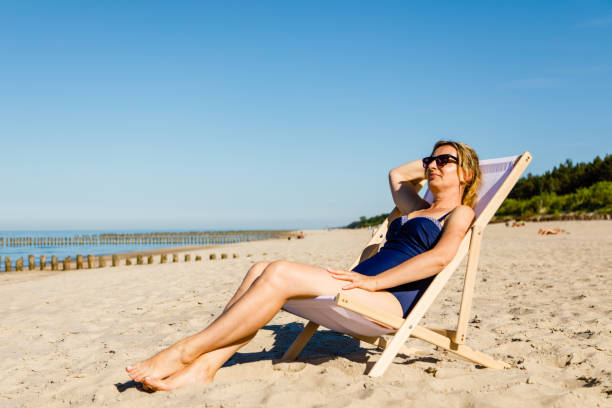 woman relaxing on beach - older women bikini stock pictures, royalty-free photos & images