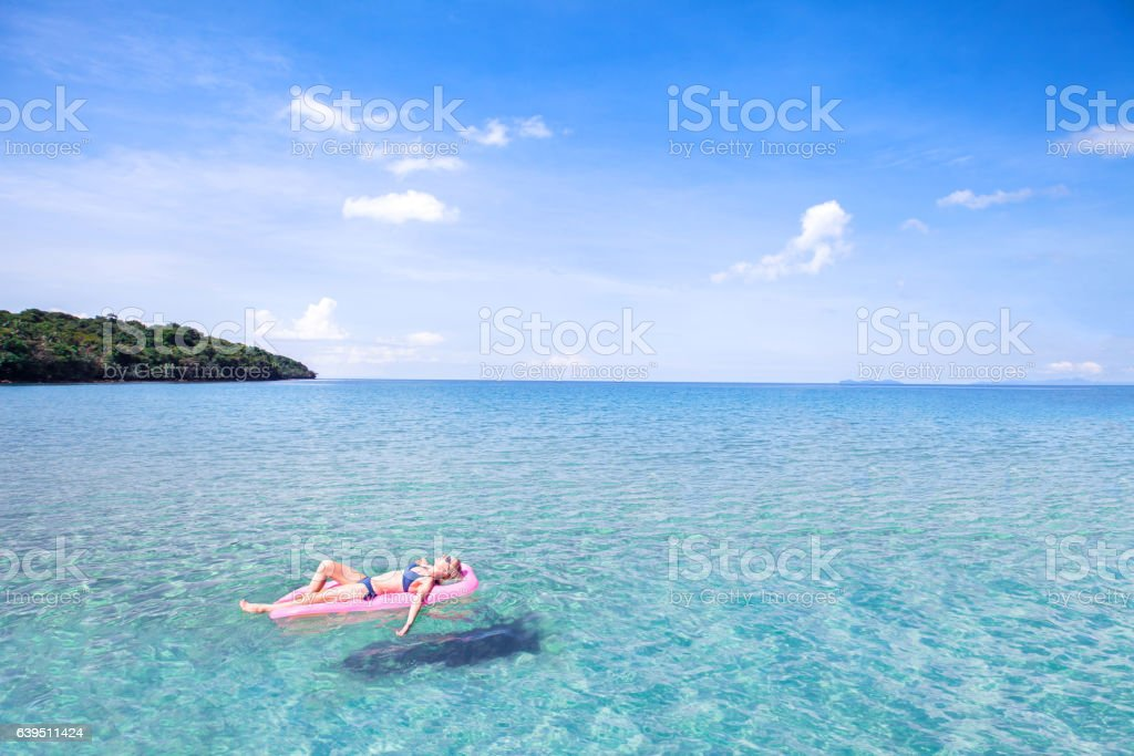 woman relaxing on beautiful beach with turquoise water, holidays stock photo