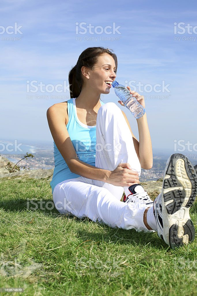 Woman relaxing on grass and drinking water royalty-free stock photo
