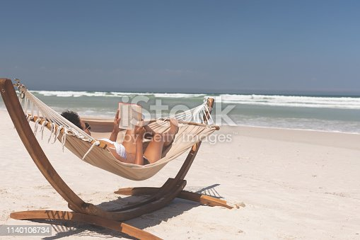 Rear view of beautiful mixed race woman relaxing on hammock at beach on a sunny day. Woman reading book while tanning in the sun.