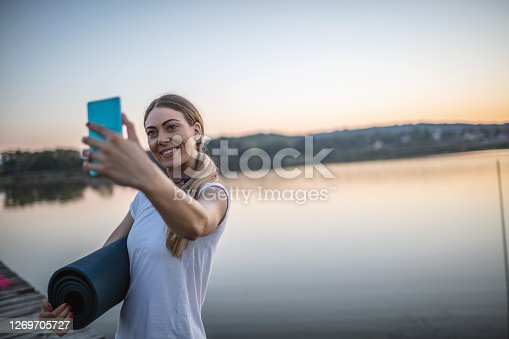 Young woman relaxing on a lake pier after exercising at sunset.She is making selfies by mobile phone.