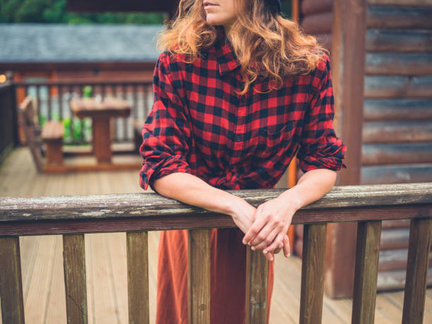 Woman relaxing on porch A young woman is relaxing on the porch of a log cabin in the country plaid shirt stock pictures, royalty-free photos & images