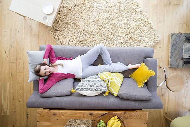 woman relaxing on sofa - yatmak stok fotoğraflar ve resimler