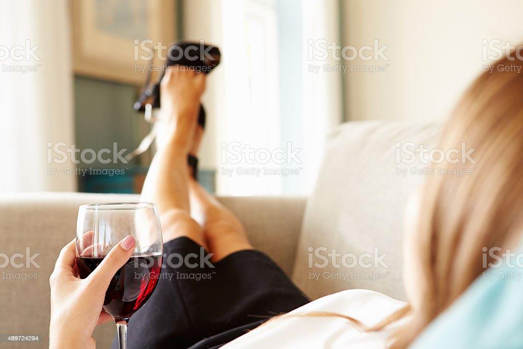 Mulher relaxando no sofá com uma taça de vinho depois do trabalho - foto de acervo