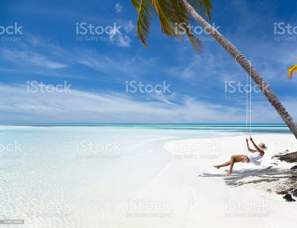 woman relaxing on swing at a tropical beach in paradise royalty-free stock photo