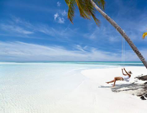 woman relaxing on swing at a tropical beach in paradise