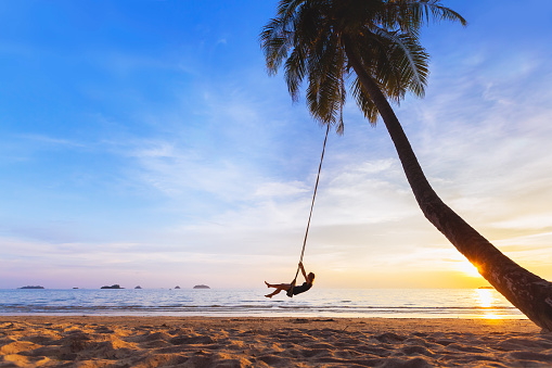 Woman relaxing on swing, tropical paradise beach at sunset, vacation