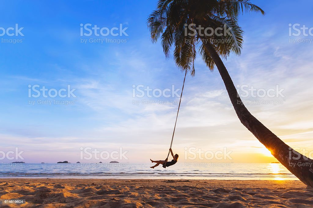 Woman relaxing on swing, tropical paradise beach at sunset, vacation stock photo