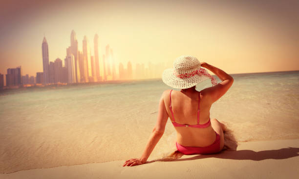 Woman relaxing on the beach in Dubai Mature woman relaxing on the beach in Dubai middle aged women in bikinis stock pictures, royalty-free photos & images